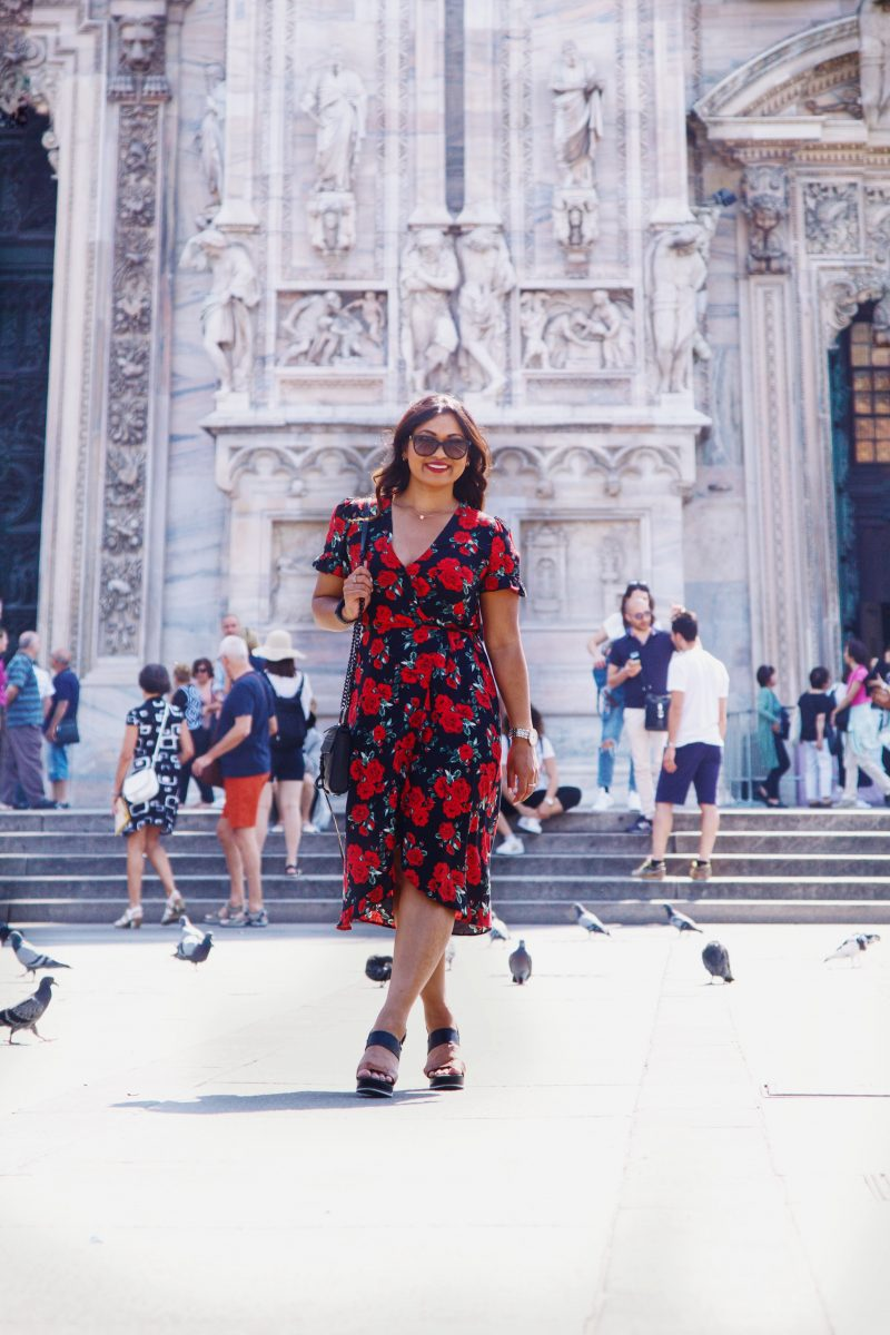 Fashion blogger outside of Duomo di Milano wearing a rose printed summer dress from Primark, black and brown wedges from Vince Camuto and a Rebecca Minkoff handbag.